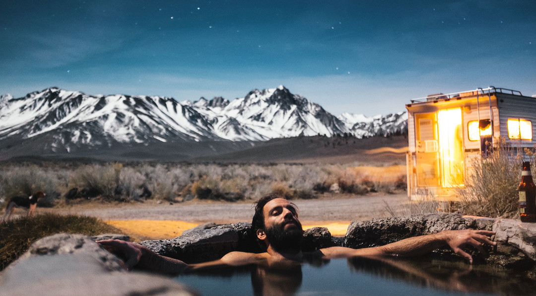 Man relaxing in an natural hot spring with his camper and a mountain range in the background