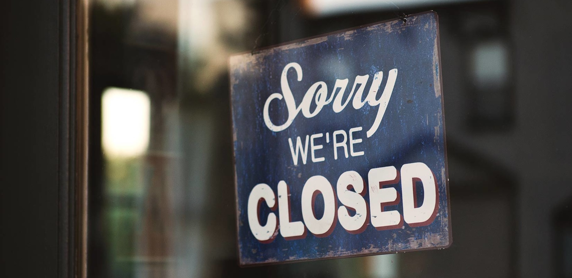 retro sign hanging in the doorway of a business saying sorry we're closed