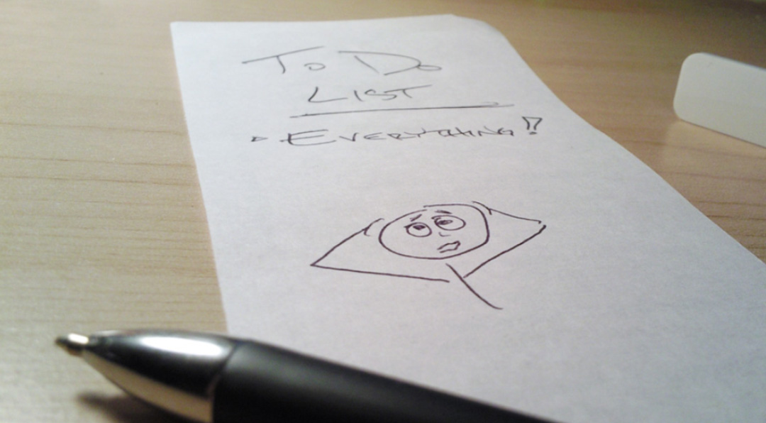 Note and pen sitting on a desk with the words to do list everything written on it with an illustration of a stickman holding his head