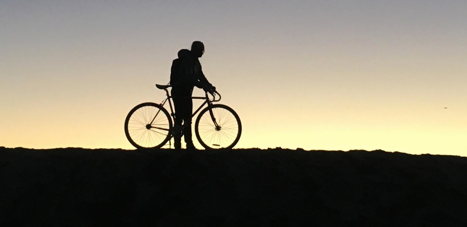 Black silhouette of a man and his bicycle against an evening sunset backdrop
