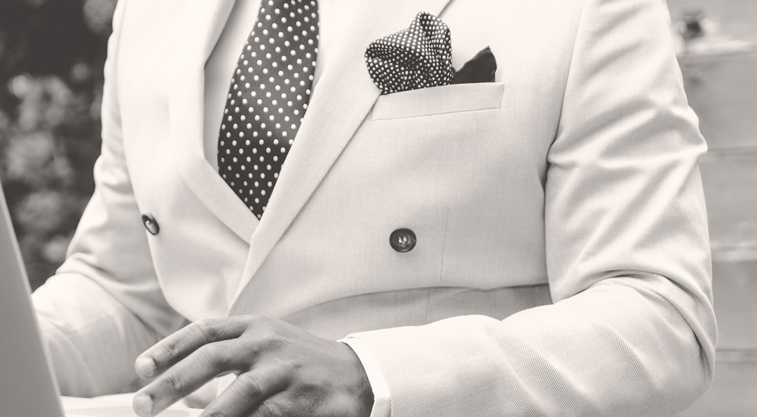 black and white image of a man wearing a classy white suit using a laptop.