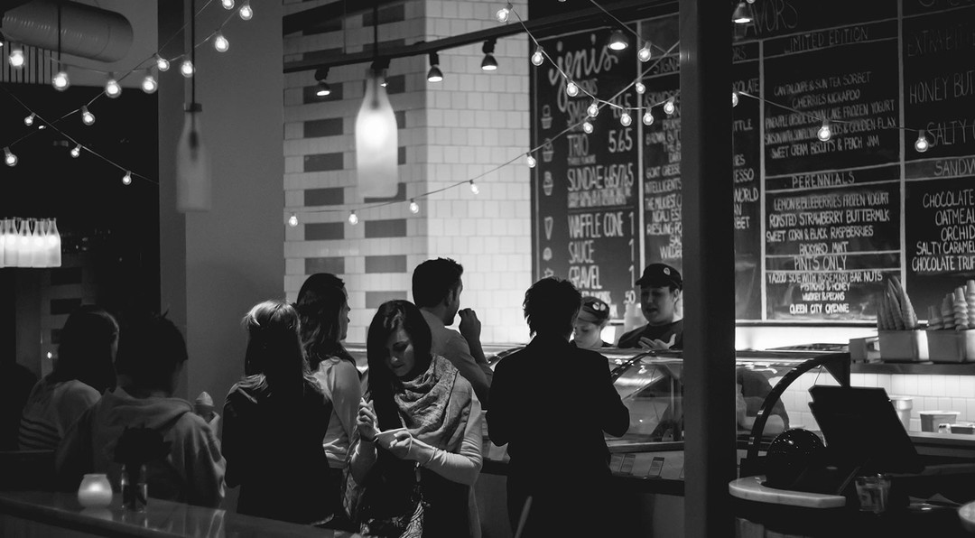 moody black and white image of a group of people ordering food from a cafe