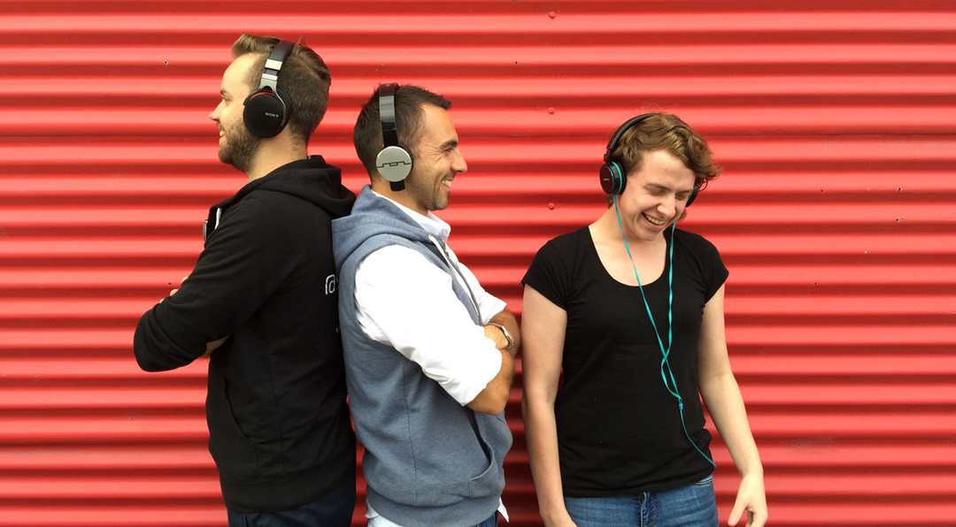 three people wearing headphones are smiling and laughing whilst standing against a bright red corrugated metal background
