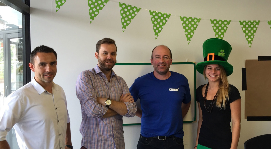 A group of four people are posing in an office along with St Patricks day decorations.