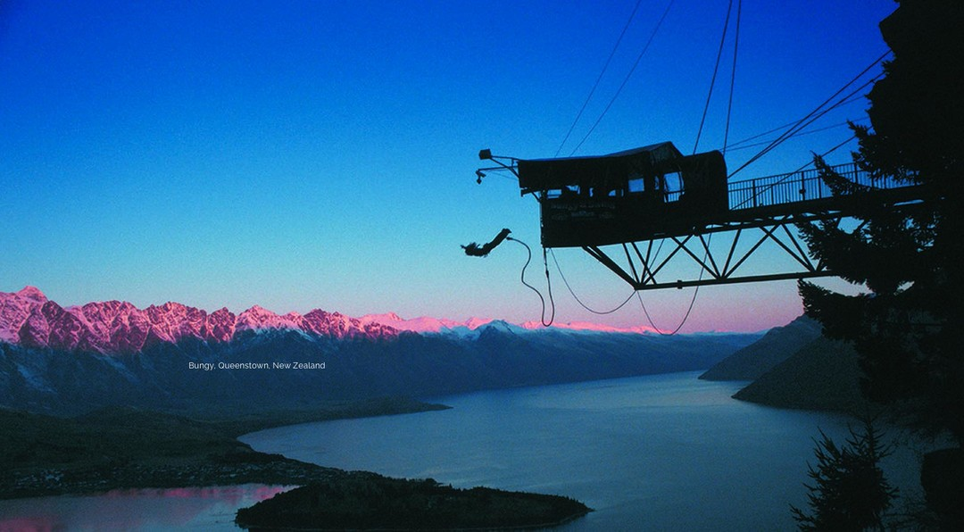 Black silhouette of a person bungy jumping from a tower, over looking a beautiful mountain range and lake at dusk.